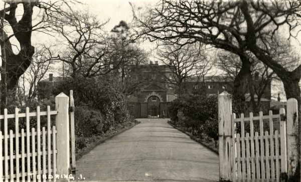 The main entrance and front driveway of the Tendring Union workhouse at Tendring Heath, Essex. A man, perhaps the workhouse porter, can just be seen. The building, designed by George Gilbert Scott and William Bonython Moffatt, was opened in 1838