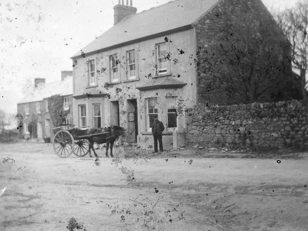 View of the main street and shop in St Davids, Pembrokeshire, Dyfed, South Wales. A man stands looking straight at the camera, with a horse and cart nearby