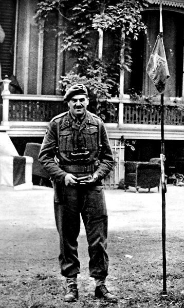 Photograph showing Major-General R.E. Urquhart, Commander of the British First Airborne Division, standing outside his headquarters near Arnhem, the Hartenstein Hotel, September 1944