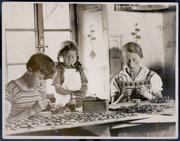 A woman and two children making Jews Harps, a primitive musical instrument, in the Steyr valley, Austria. They are bought by a Birmingham firm for export to Aborigines