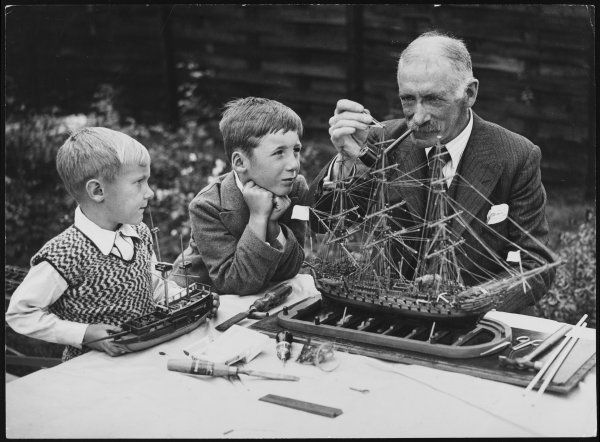 Grandfather teaches his grandsons how to thread rigging onto the model ship he is making. The two well- behaved boys look captivated
