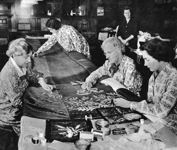 Women at the Royal School of Needlework at Prince's Gate, Kensington, London, seen working on the Coronation robe for Queen Elizabeth II. The robe of pure silk was embroidered with a design chosen by the Queen. On the left of the table is Miss Violet Wise