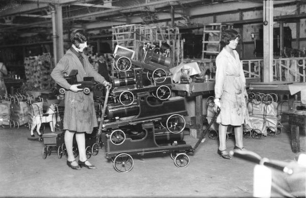 In a London factory, two women workers attend to the last minute orders for Christmas; here a stack of toy locomotive engines await dispatch