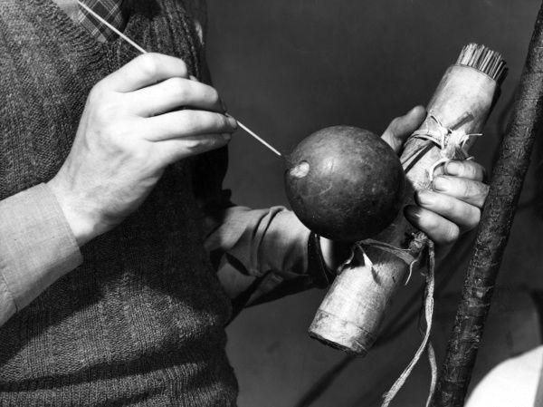 The war weapons of the Makusi tribe of the Rupununi River, British Guyana. The round gourd contains the curare poison. The dart is dipped in this and blown with the pipe. Date: 1930s