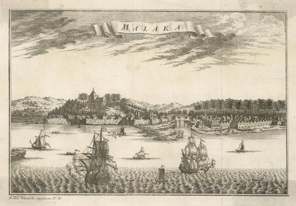 A view of Malaka from the sea showing sailing ships and other smaller vessels, rows of small houses, a walled area of the town & a building set up on stilts in between