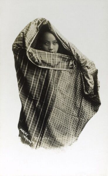 Malaysia - Local woman wrapped in traditional patterned cloth. Date: circa 1910s