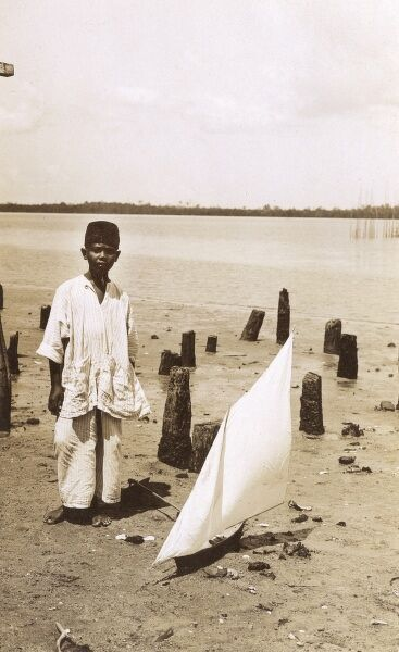 A Malaysian boy with a toy yacht on the banks of a lake. Date: circa 1920s
