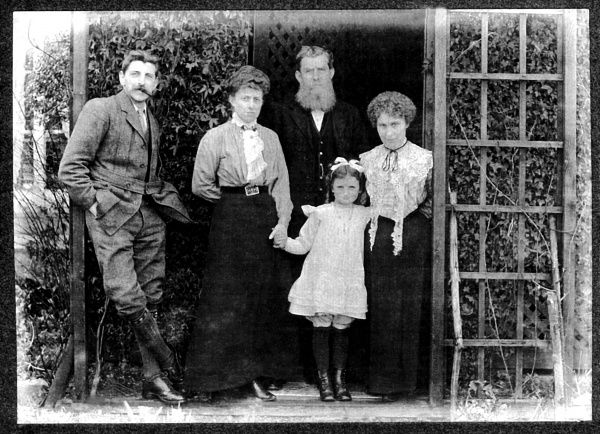 Members of the Malby family (four adults and a child) pose for a group photo in a garden