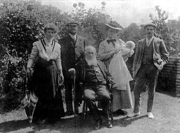 Members of the Malby family (five adults and a baby) pose for a group photo in their garden at Woodford, Essex. On the far right is Reginald Malby (1882-1924), official photographer to the Royal Horticultural Society. Next to him is his wife Eleanor