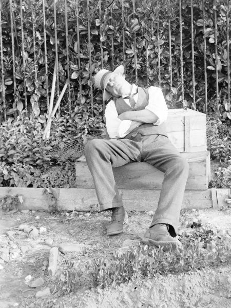 A man in a straw hat and shirtsleeves, asleep in a garden, Mid Wales. He appears to have been doing some gardening, as he has left his clippers in front of the railings behind him. Gardening is so exhausting!