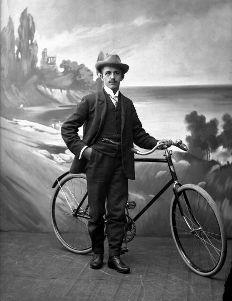 Posed man with his bicycle, 1910. Date: 1910