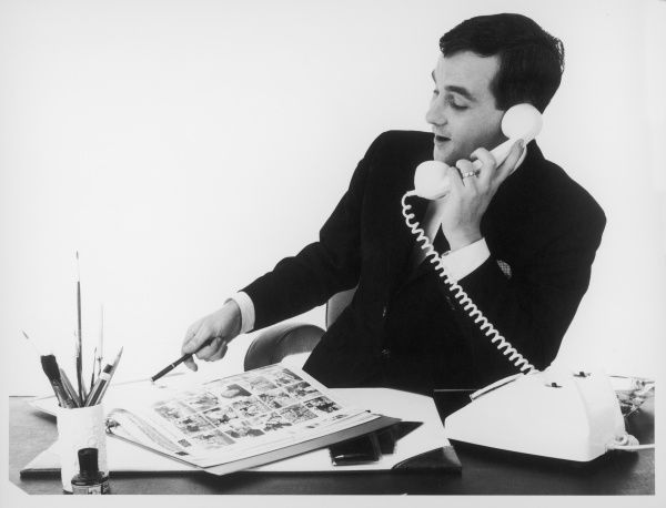 A man in a suit sits at his desk and talks on the telephone as he points to some photographs in the Ad Lib Catalogue