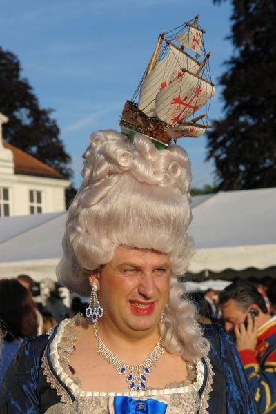 A man in drag, including a white wig with a model ship on top, at a rococo festival in Haimhausen, just north of Munich, Bavaria, Germany