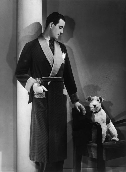 Man models a wool jersey dressing gown, and his wire- haired fox terrier poses for the camera