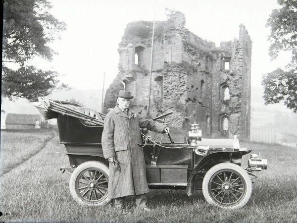 An elderly country gentleman with a very early motor car (roof folded back) in front of the ruins of Crickhowell Castle, Crickhowell, Powys, Mid Wales