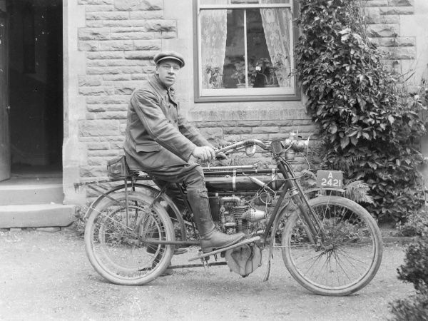 A man on an early motorcycle, possibly a Triumph, registration A 2421, in front of a house