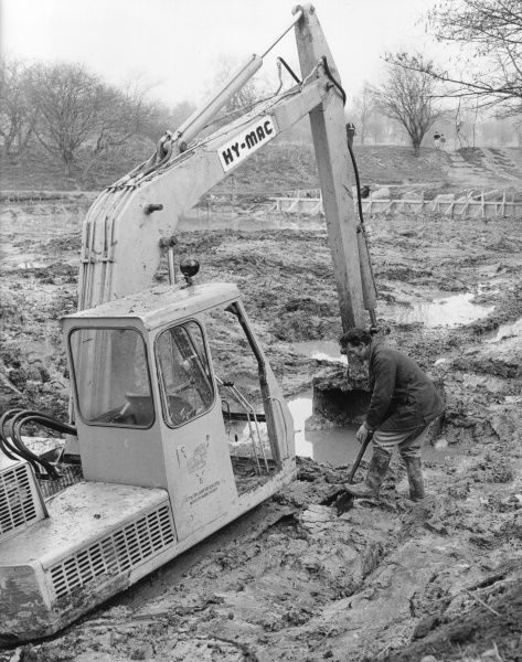 A man working next to a mechanical Hy-Mac digger in a muddy field. Perhaps the digger has got stuck in the mud, and he is trying to dig it out