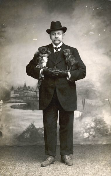 A man in a black suit with a pekingese dog under each arm
