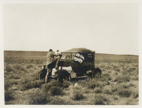 A man pouring water into a car radiator in the middle of dry scrubland, somewhere in the Middle East. There is a Union flag flying on the front of the car