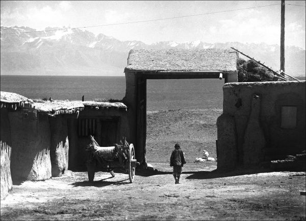 A man in a walled settlement surrounded by mountains in Kashgar, western China. Date: 1932