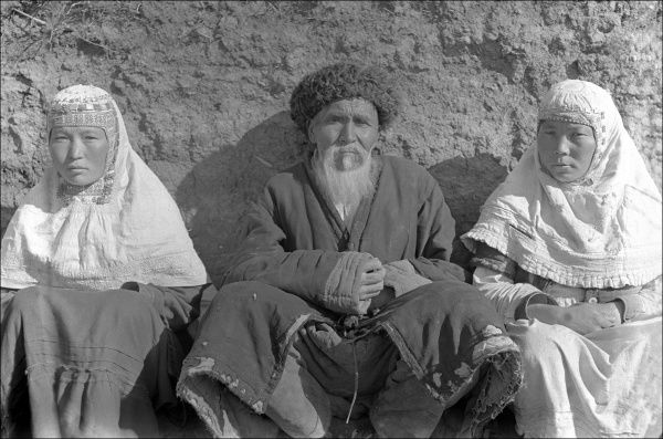 A man and two women wearing national costume in either Kashgar (western China) or Kyrgyzstan (Central Asia, west of China)