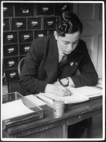 A young man making an entry in a ledger with a fountain pen. He sits at a desk with a wire 'in-tray' and stacks of card index drawers behind him