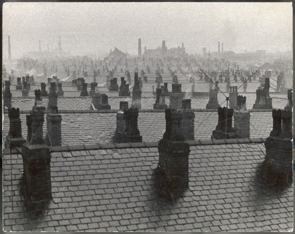 Manchester skyline - an urban cityscape of rooftops and chimney stacks, the air grey with industrial smog