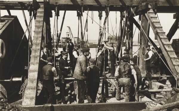 Workmen operate a temporary pulley-based device used in the process of the construction of a new dock for the Manchester Ship Canal