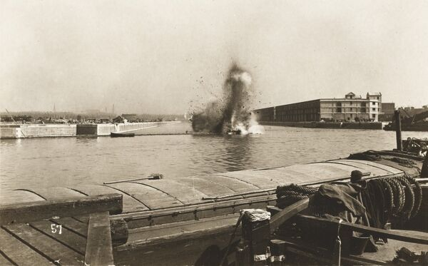The dramatic opening of a new dock on the Manchester Ship Canal. A charge is detonated to break a temporary levee across the entrance to the new dock