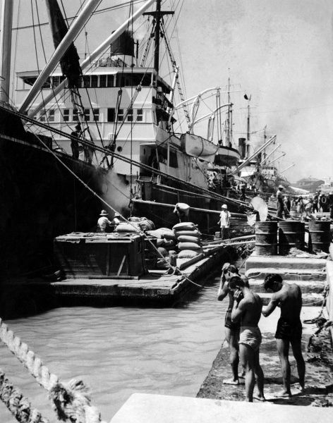 Unloading a shipment of cargo from ships in Manila docks, Philippines. Three young men in shorts wipe the sweat from themselves in the heat. Date: late 1930s