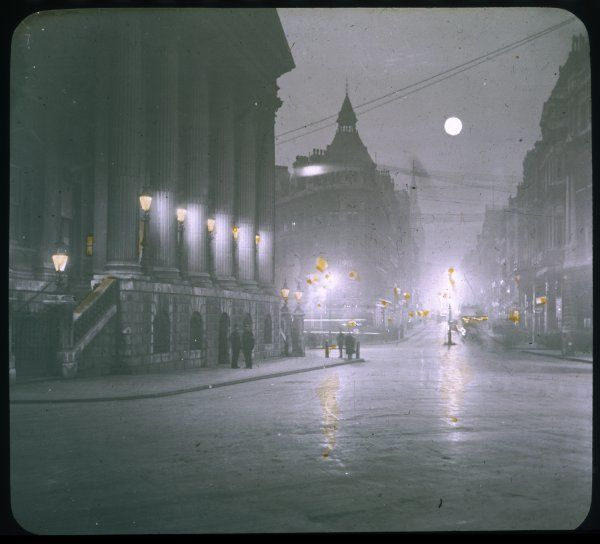 A street scene of Mansion House at night with a full moon
