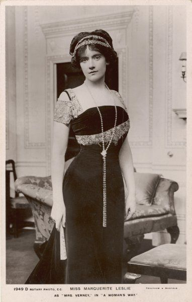 The S-bend silhouette is still discernable in this velvet gown with square corsage & crochet or lace trim. N.B bandeau in her hair & a long string of knotted pearls