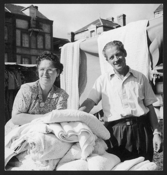 A married couple on a market stall, selling bedspreads, towels, throws, etc