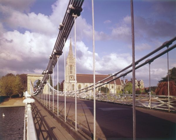 A delighful glimpse of All Saints Church, Marlow, Buckinghamshire, England, seen through the suspension bridge over the River Thames. Date: 1960s
