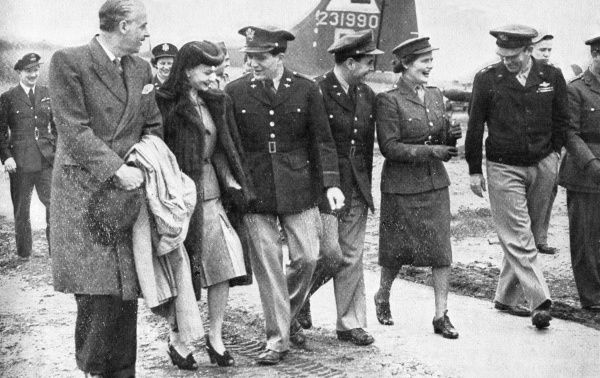 After breaking a bottle of Coca-Cola across the nose of a new Fortress aircraft and naming it 'Stage Door Canteen', Miss Mary Churchill left the airfield with some of the officers. On the left are Alfred Lunt, the actor, and Vivien Leigh
