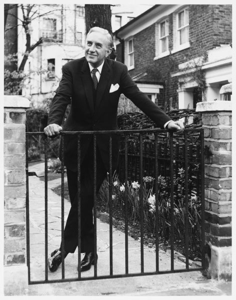 A mature man in a three piece suit poses behind a garden gate