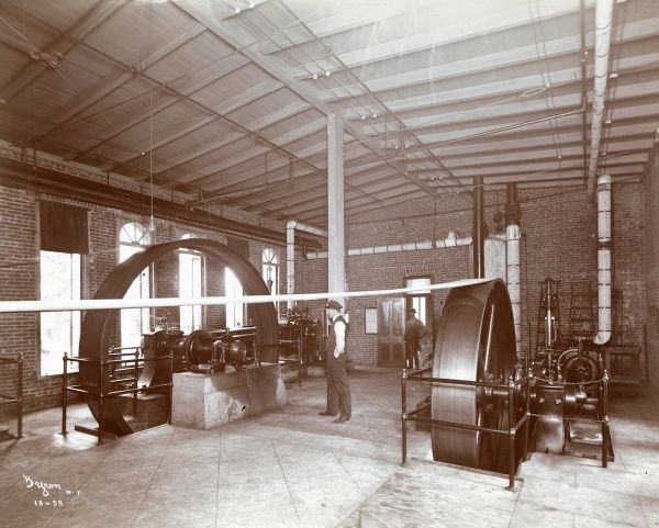 Maxwell & Briscoe. Workers watching two large belt-driving wheels that power the Maxwell