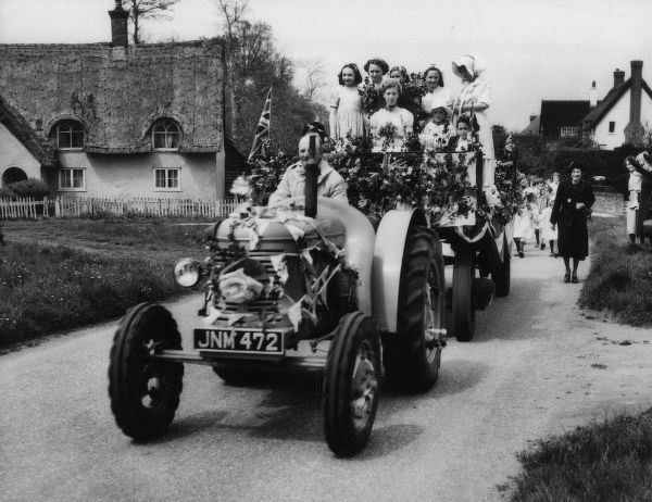 Traditional May Day festivities at Ickwell, Bedfordshire, England. Here, the May Queen arrives on the village green in luxury - by tractor! Date: 1950s