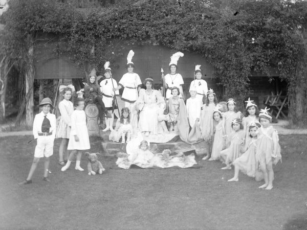 A group of children dressed as nymphs or fairies, and four attendants with feathered headdresses, with a young woman, probably the May Queen, enthroned at the centre
