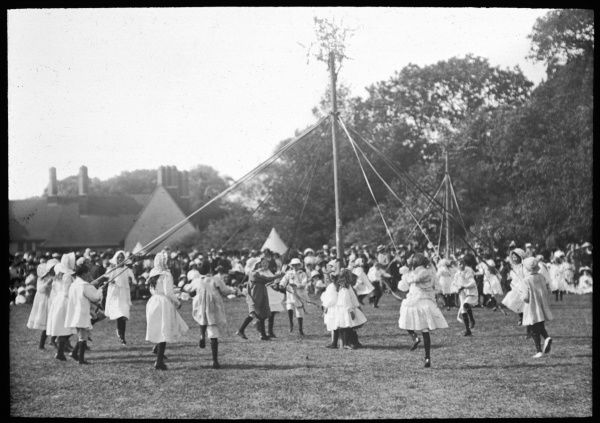 Children dance round the pole at an English country fete