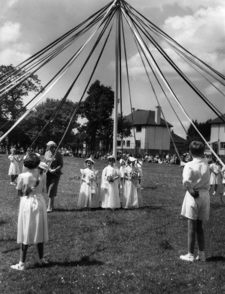 A glimspe of the May Queen, through the Maypole and dancers at the 'Miracle of Spring' celebrations at Kingsteignton, south Devon, England. Date: 1950s