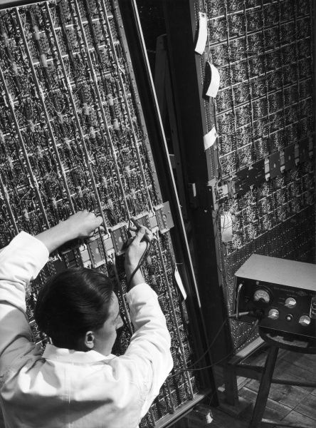 A man measures the current running through a large electronic device, possibly an early computer or exchange. Photograph by Heinz Zinram