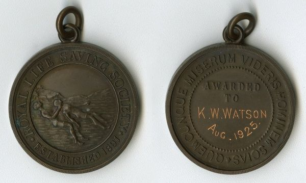 Medal of the Royal Life Saving Society (established 1891) awarded to K. W. Watson, featuring a rescue taking place with two figures in the water. On the reverse is a Latin inscription: Quemcunque Miserum Videris Hominem Scias. Date: August 1925