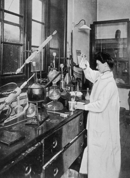 A female medical student studies a beaker in the chemistry laboratory of the Royal Free Hospital, London
