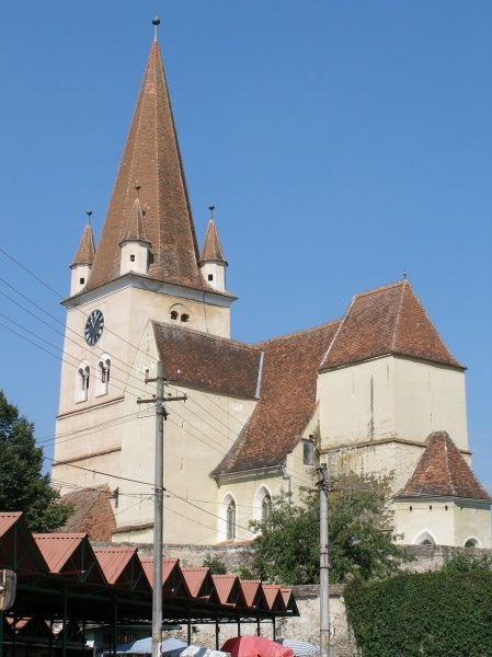 View of a medieval fortified church in Cisnadie (Heltau), Sibiu, in Transylvania, Romania, with a street market just visible below. The church was built in the 12th century and fortified in the 15th