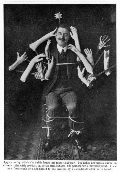 The British magician William S Marriott demonstrates how spiritualists may create the illusion of spirit hands at a seance. The dummy hands are painted with luminous paint and fixed on a framework, passed to the subject after he has been bound