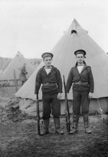 Two members of the Royal Naval Division (RND), outside their tent at a camp holding their rifles at their sides. The service was formed in September 1914 to fight alongside the army during the First World War, and was disbanded in June 1919