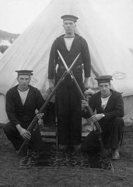 Three members of the Royal Naval Division (RND), outside their tent at a camp with rifles crossed. The service was formed in September 1914 to fight alongside the army during the First World War, and was disbanded in June 1919