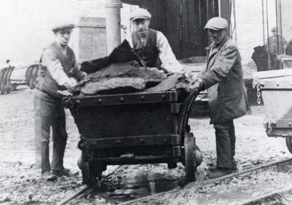 Three men with a loaded dram (truck) of coal at Hook Colliery, near Haverfordwest, Pembrokeshire, South Wales