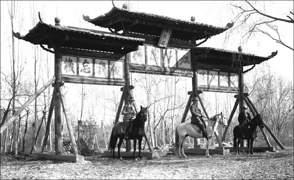 Three men on horseback in front of three structures with oriental style roofs, in Kashgar, western China. Photograph by Ralph Ponsonby Watts